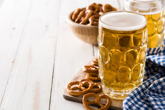 Oktoberfest beer and pretzel on white wooden table. Copyspace