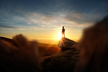 Leadership And Goals. A man standning on top of a mountain watching the sun set. Conceptual photo composite.