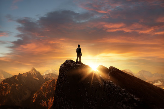 A man standing on top of a mountain as the sun sets. Goals and achievements concept photo composite.