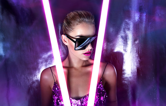 Portrait of a beautiful young tanned girl in big sunglasses in a pink shiny dress in the studio on a silver background with a pink and purple hue. Glowing fluorescent lamps in the face.