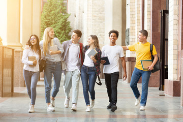 Happy students walking together in campus, having break Wall mural
