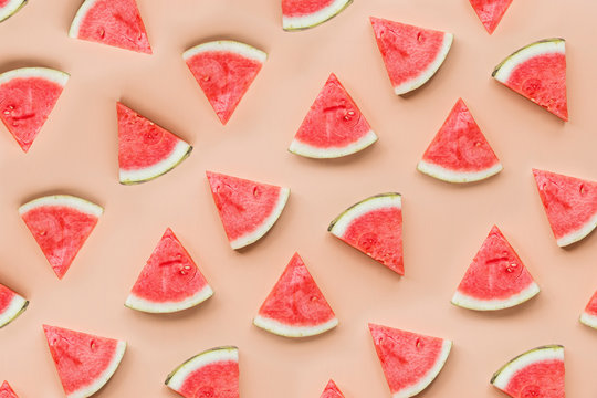 Creative flat lay top view of fresh watermelon slices on orange table background with copy space. Minimal summer fruits pattern for blog or recipe book. Healthy food and diet concept.
