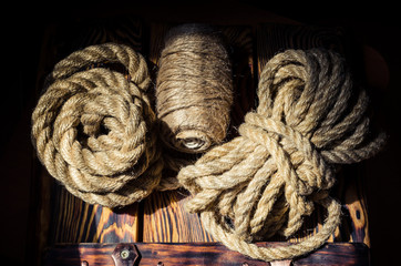 Several types of hemp and jute rope on a brutal wooden background. Shooting from top to bottom. Soft focus.