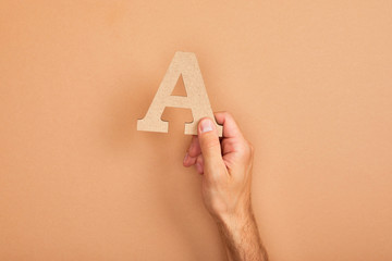 cropped view of man holding paper cut letter A on beige background