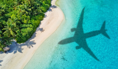 Spoed Fotobehang Strand Travel concept with airplane shadow and beach