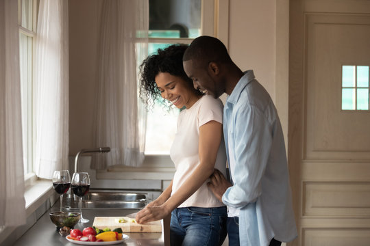 African romantic couple cooking together dinner in the kitchen