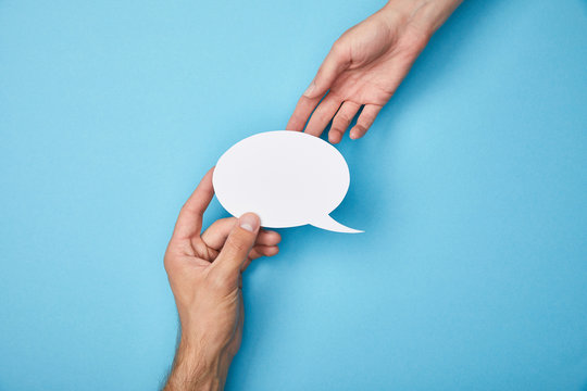 cropped view of man giving white empty speech bubble to woman on blue background