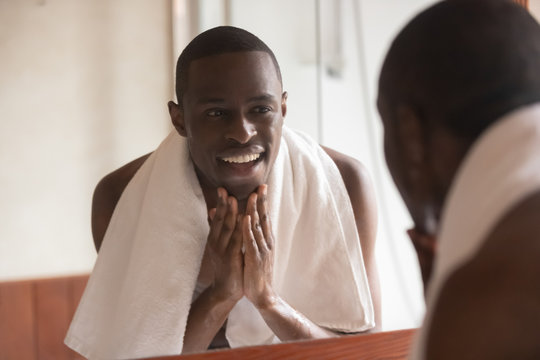 African man looking in mirror cleaning face after shaving