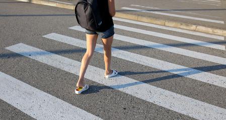Legs of a girl walking along a pedestrian crossing Fotobehang