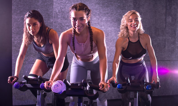 Cheerful girls riding exercise bikes together on cycling class indoors