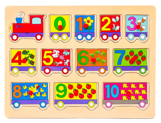 Wooden puzzle in form of train with numbers and arithmetic signs with pictures of items. Children's hand takes the figures from the puzzle. Preschool educational game for the game for learning numbers