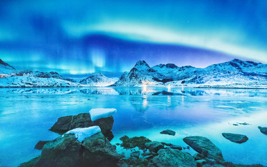 Amazing scene of Northern Lights (Aurora Borealis) on Lofoten Islands in Norway. Beautiful colorful landscape of polar lights on starry sky reflected in the fjord on Lofotens.