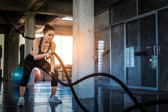 Young asian girl training with battle rope in cross fit gym, Battle ropes session.Strong asian woman exercising with battle ropes at the gym with male trainer.