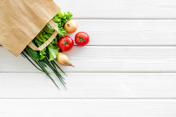 Buying fresh vegetables in paper bag on white wooden background top view copyspace