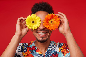 Close up smiling young African American guy, wears in Hawaiian shirt, looks at the camera trough flowers with happy expression, holds yellow and red flowers, stands over red background.
