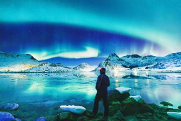 Foto op Plexiglas Noorderlicht Silhouette of tourist observing natural wonder Northern Lights (Aurora Polaris) at glacier lagoon bank on Lofoten Islands Archipelago in Norway over polar circle. Beautiful landscape.