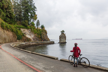Vancouver cyclist biking woman on bike road around Stanley Park, famous attraction tourist activity in British Columbia, Canada. Autumn lifestyle. Wall mural