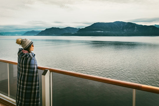 Alaska cruise travel luxury vacation woman watching inside passage scenic cruising day on balcony deck enjoying view of mountains and nature landscape. Asian girl tourist with wool blanket.