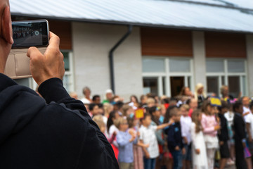 Tumba, Sweden - june.14.2018: A man takes pictures of children on a mobile phone. Circa Salem kommun.
