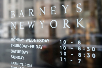 The Barneys New York logo is seen in a door window outside the luxury department store in New York