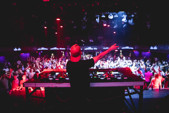 DJ performing for nightclub, view from behind