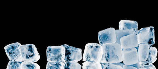Pieces of frosty ice cubes on black reflective surface background.