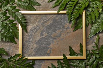 empty golden frame on stone background with copy space and green fern leaves Wall mural