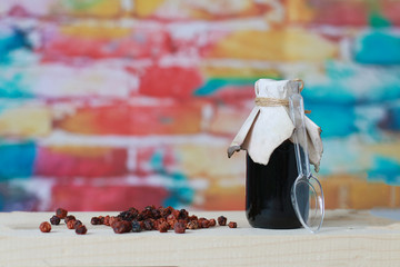 dark glass syrup bottle and rosehip berries lie on a wooden shelf on a brick blurred background