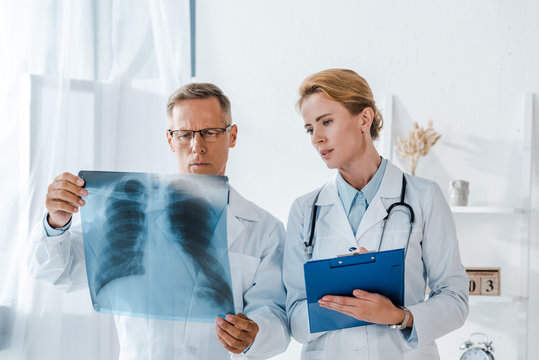 attractive doctor holding clipboard and looking at x-ray near coworker