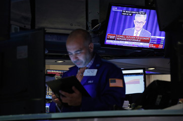 A trader looks on as a screen shows Federal Reserve Chairman Jerome Powell's news conference after the U.S. Federal Reserve interest rates announcement on the floor of the New York Stock Exchange (NYSE) in New York