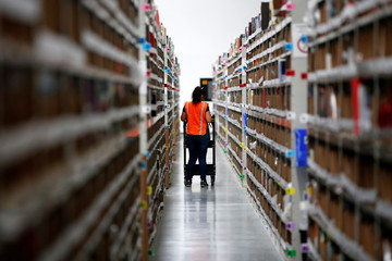 An employee looks for items in one of the corridors at the new Amazon warehouse during its opening announcement on the outskirts of Mexico City
