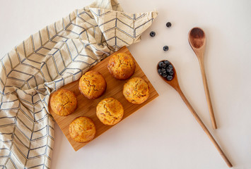 Top view of carrot muffins on a wooden board with tea towel and wooden spoons and blueberries on a white background