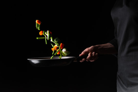 Close-up, chef preparing vegetables in a skillet frying them. Hotel business and the menu in restaurants, the book of recipes. On a black background