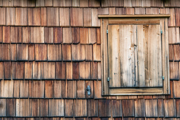 closed shutter and weathered and faded from the sun wooden shingles that are the facade of an alpine house. Closed window and shutter on wooden texture in shades of gray and orange.
