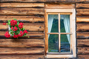 A fragment of a wooden alpine house. The wall made of logs, window and red flowers hanging on the wall