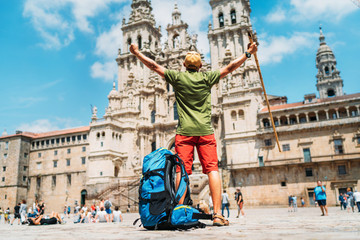 Young backpacker man pilgrim standing with raised arms on the Obradeiro square (plaza) - the main square in Santiago de Compostela as a end of his Camino de Santiago pilgrimage. Wall mural