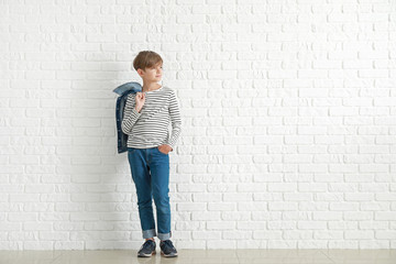 Stylish boy in jeans clothes near white brick wall