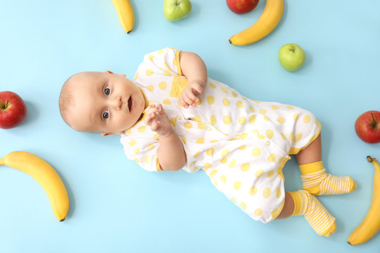 Adorable little baby with fruits on color background