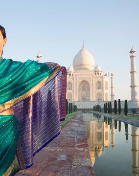 Woman in sari standing in front of Taj Mahal palace