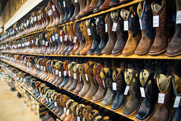 View of brown and black leather cowboy boots on shelves in shop Wall mural