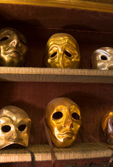 Close up of golden carnival masks on shelfs
