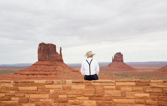 Rear view of man in cowboy hat sitting on retaining wall