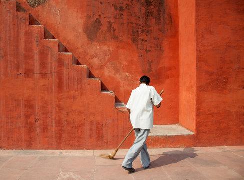 Rear view of man sweeping floor in front of orange building