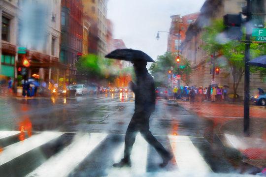 Man with umbrella walking on pedestrian crossing in rain