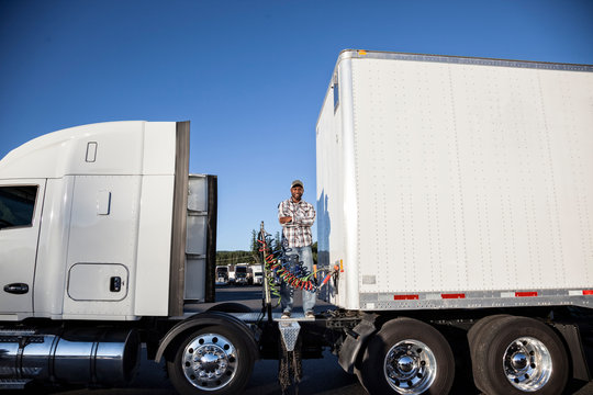 Man standing on semi trailer truck at truck stop