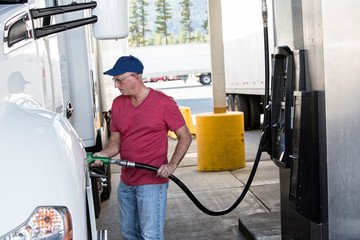 Truck driver filling truck with diesel fuel at truck stop