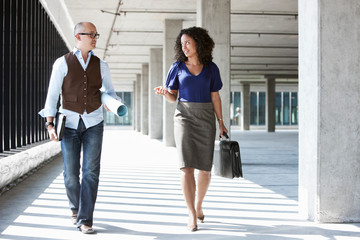 Businesswoman and businessman walking in office space