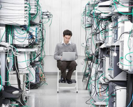 Technician working on laptop in computer server room