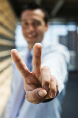 Businessman showing victory sign