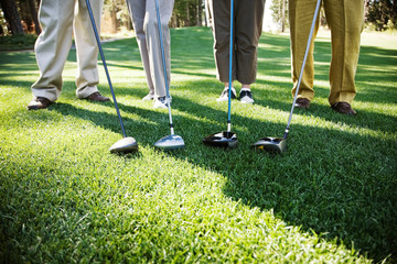 Low section of golfers standing with golf club